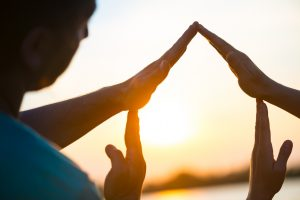 Young couple making a conceptual house symbol with hands against sunset. Real estate, housing, construction industry, architecture and design concept. Isolated with clipping path.